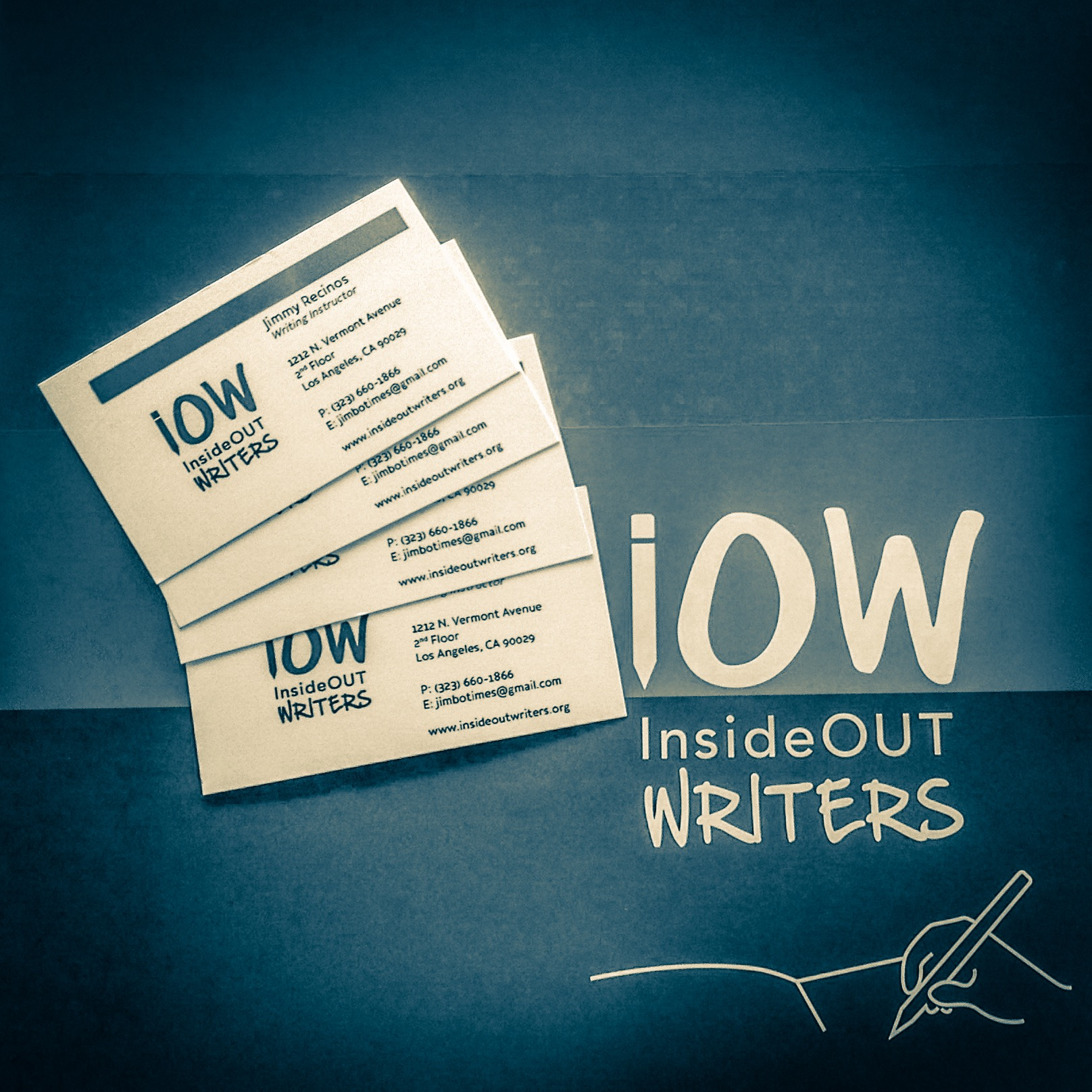 Inside Out Writers business cards atop a folder from the organization