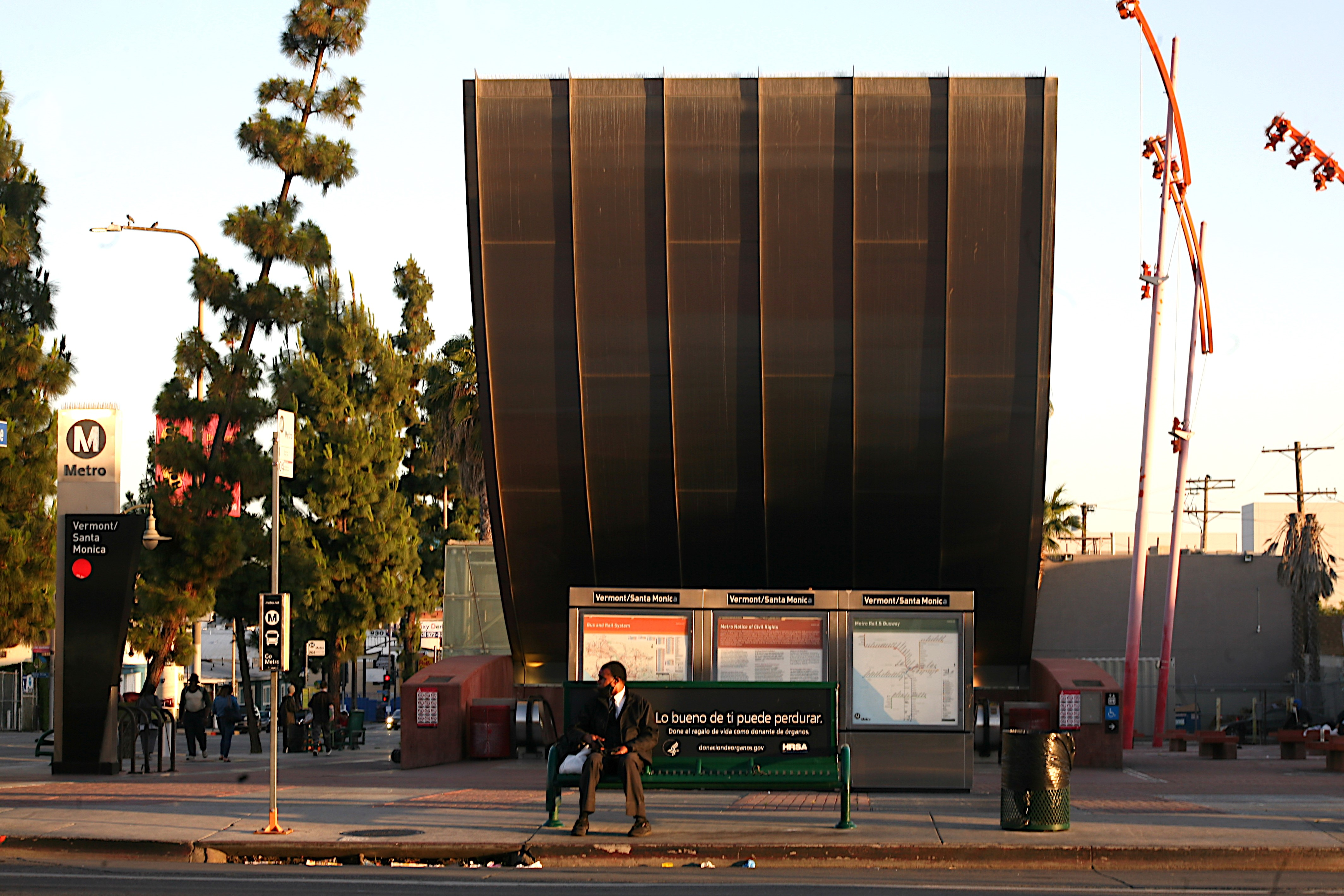 A man sits waiting for the bus at the Vermont and Santa Monica transit center.