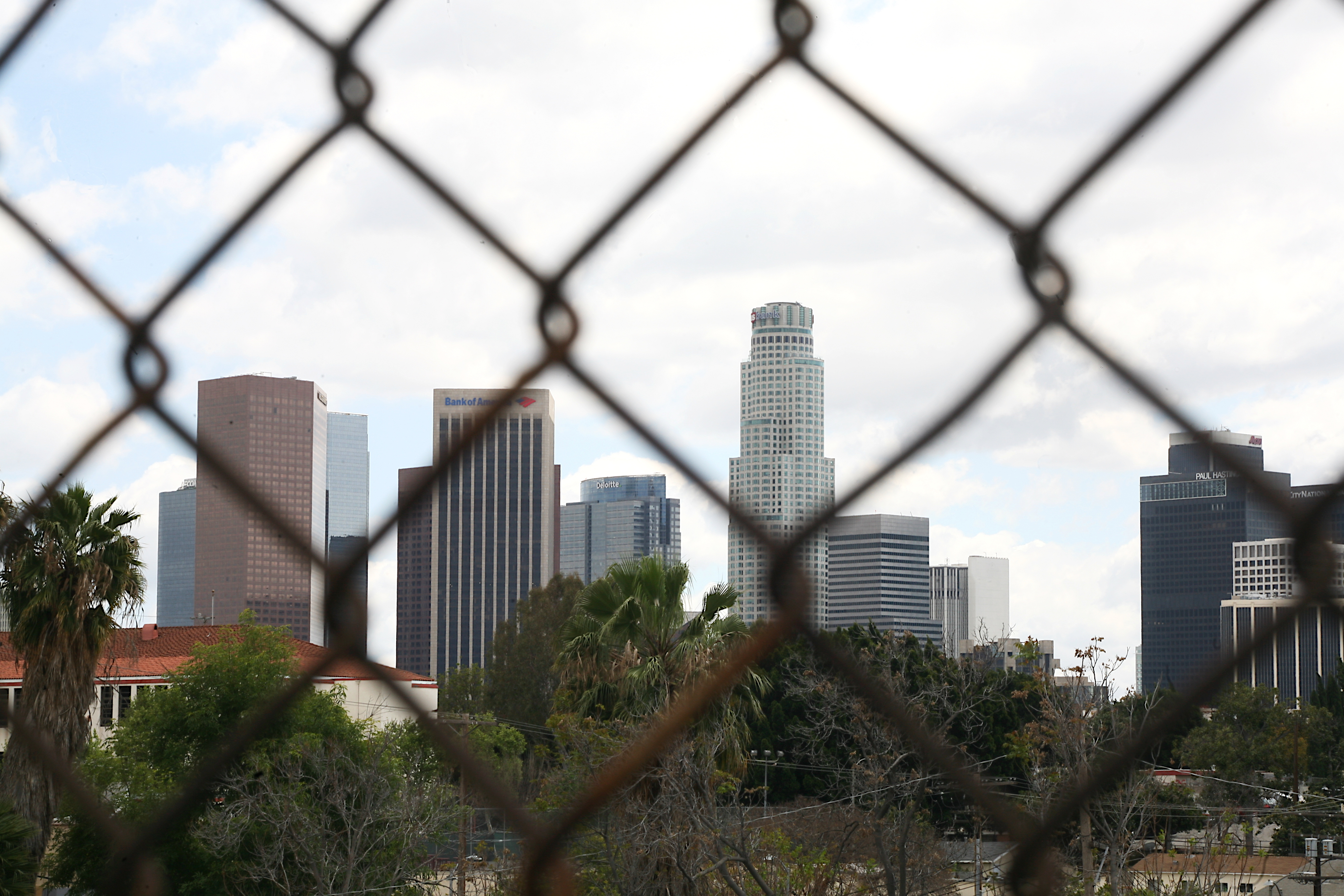 The downtown Skyline appears behind a fence separating the 101 freeway from Echo Park