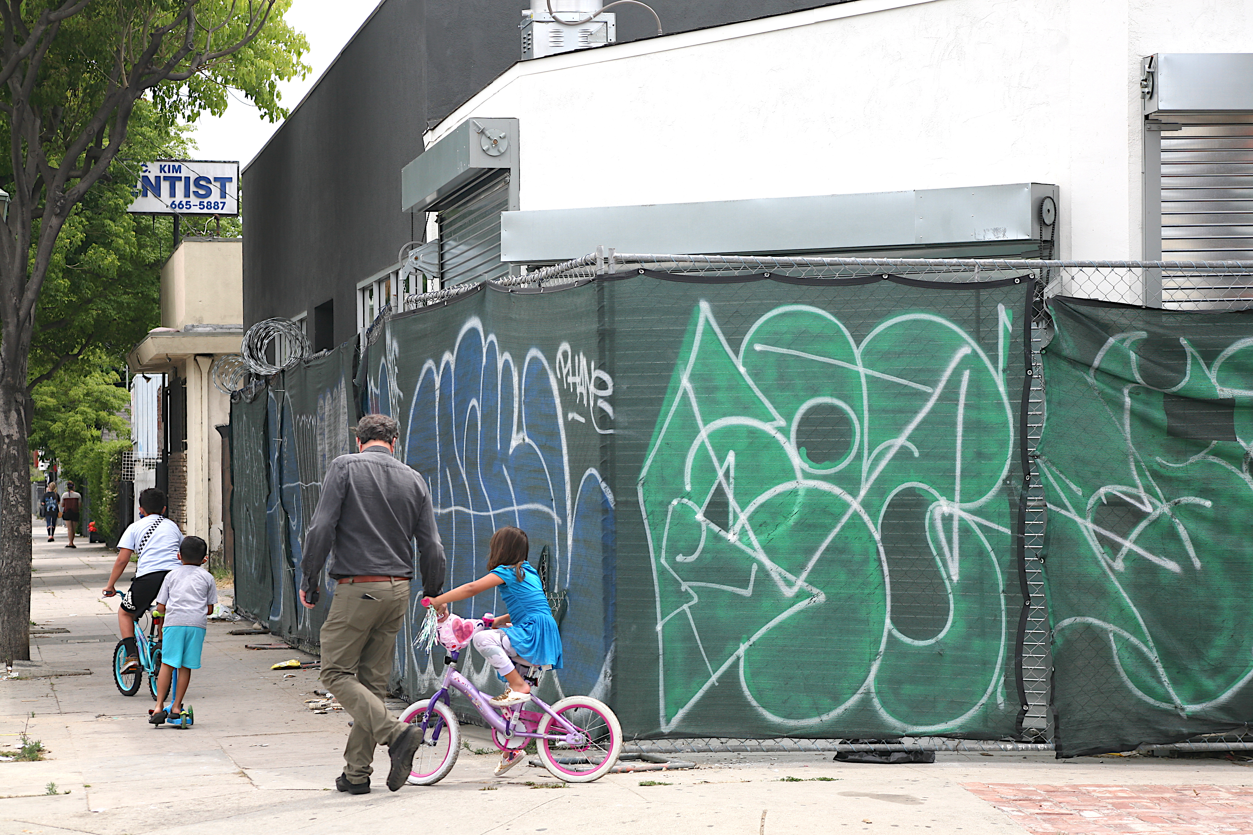 A group of kids ride their bikes and scooters as papa watches along near the former Super Pan Bakery